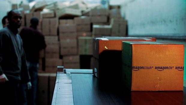 Funcionários empilham pacotes da Amazon para entrega no Reino Unido (Foto: Bruno Vincent/Getty Images)