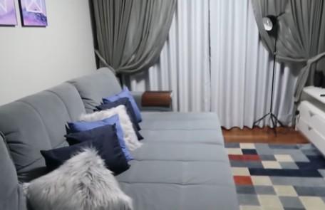 A sala de TV tem sofá grande e tapete colorido Reprodução