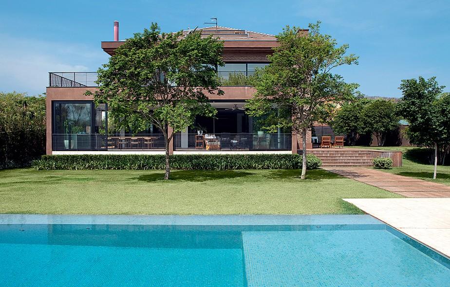 Na fachada dos fundos, surge o quintal com piscina. Junto ao guarda-corpo, estão plantadas renques de murtas e agapantos. Em frente, árvores mirindibas. Projeto da arquiteta Clarissa Strauss