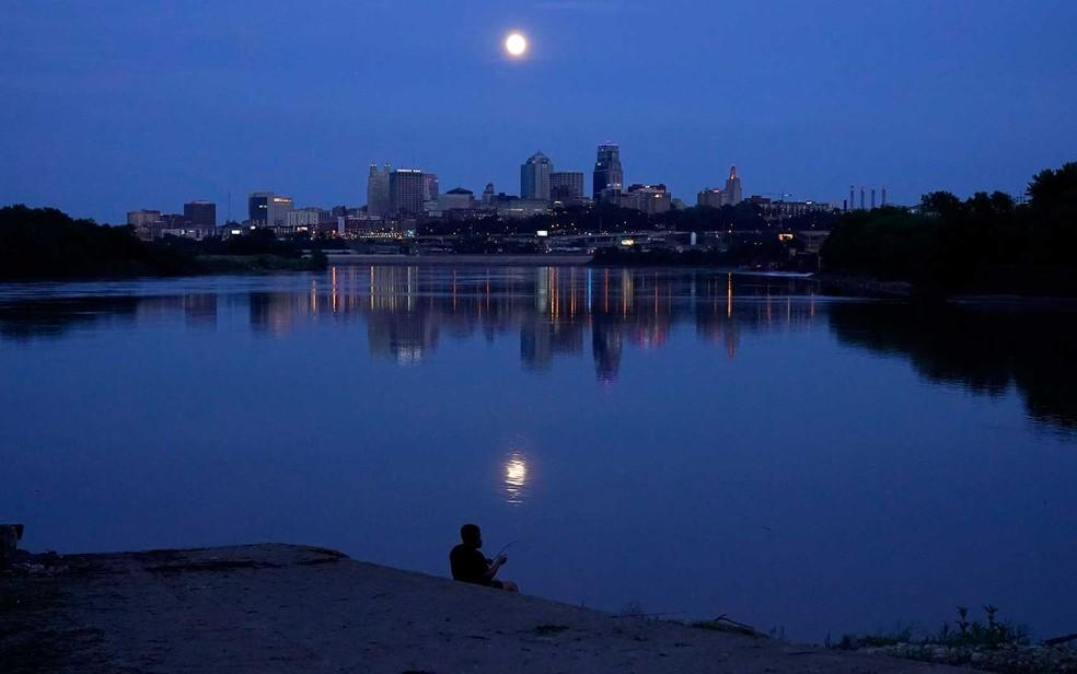 Homem pesca no rio Missouri enquanto a lua quase cheia sobe além do horizonte em Kansas City, Missouri — Foto: Charlie Riedel / AP Photo