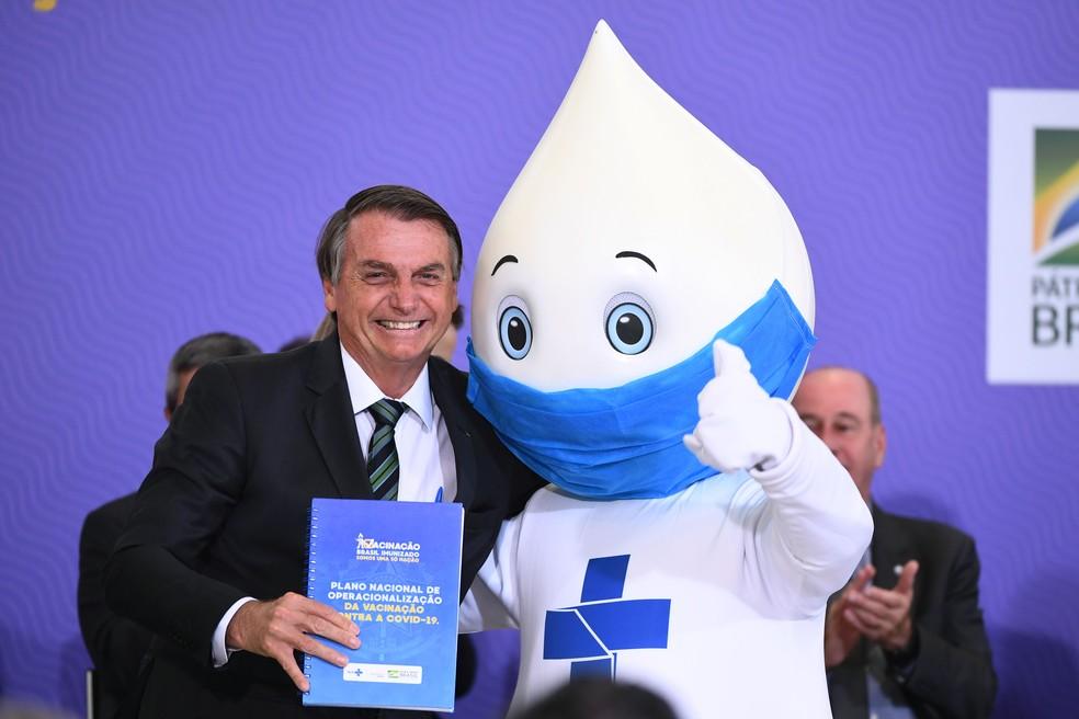 Sem máscara, o presidente Jair Bolsonaro posou ao lado do Zé Gotinha durante o lançamento do plano nacional de vacinação contra a Covid — Foto: Evaristo Sá/AFP