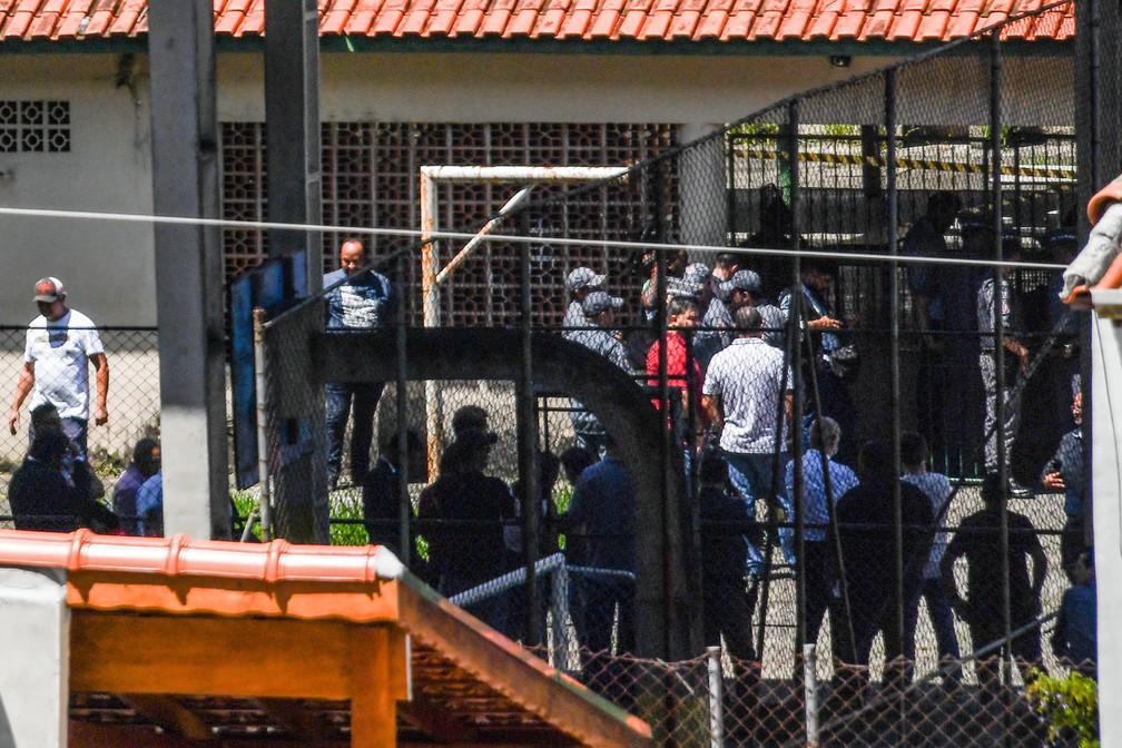 Familiares e amigos aguardam por informações na entrada da  Escola Estadual Raul Brasil em Suzano, na Grande São Paulo. Dois criminosos encapuzados mataram oito pessoas no local e cometeram suicídio em seguida  — Foto: Nelson Almeida/AFP