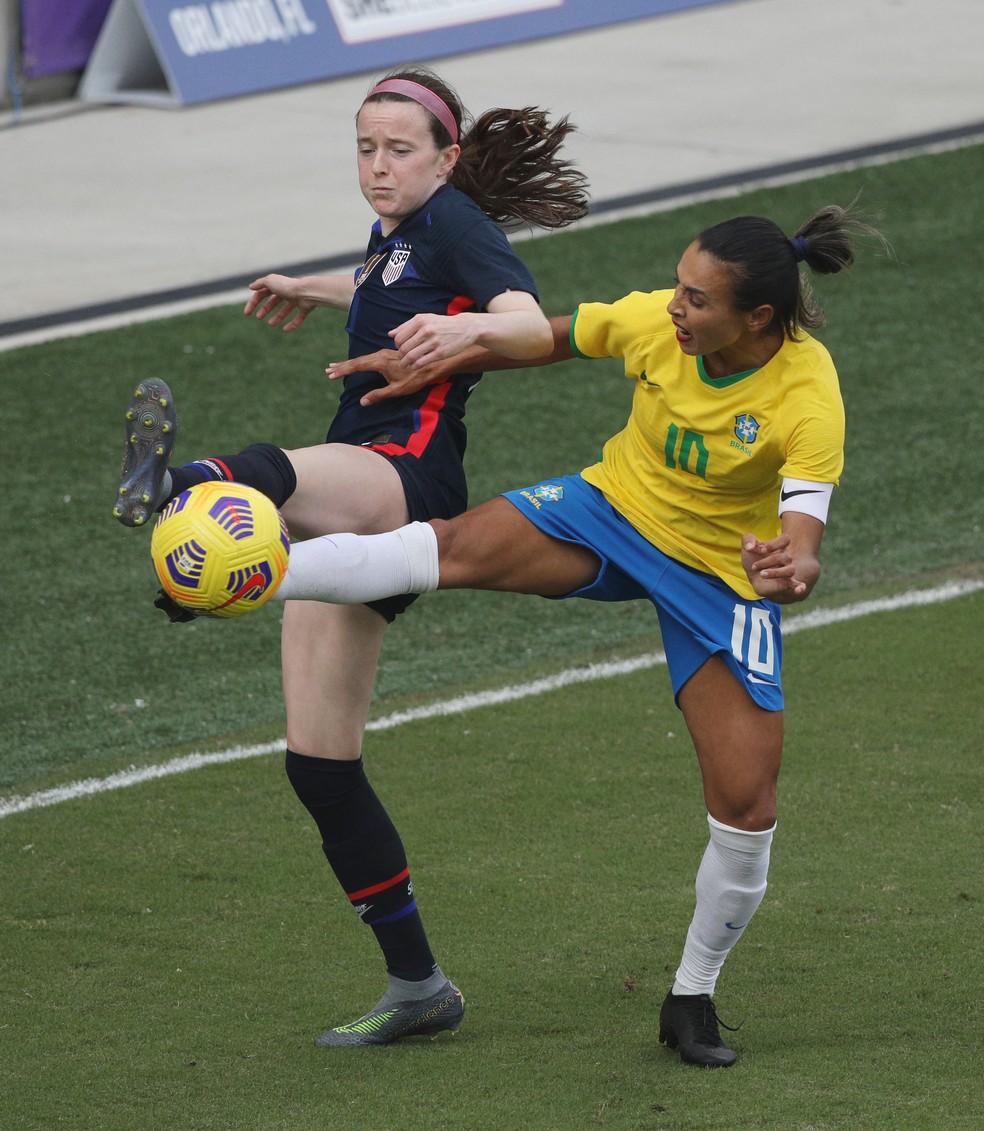 Rose Lavelle e Marta disputam a bola no amistoso entre EUA e Brasil — Foto: GREGG NEWTON / AFP