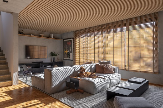 Décor do dia: sala de estar tem piso de taco e teto de painel ripado