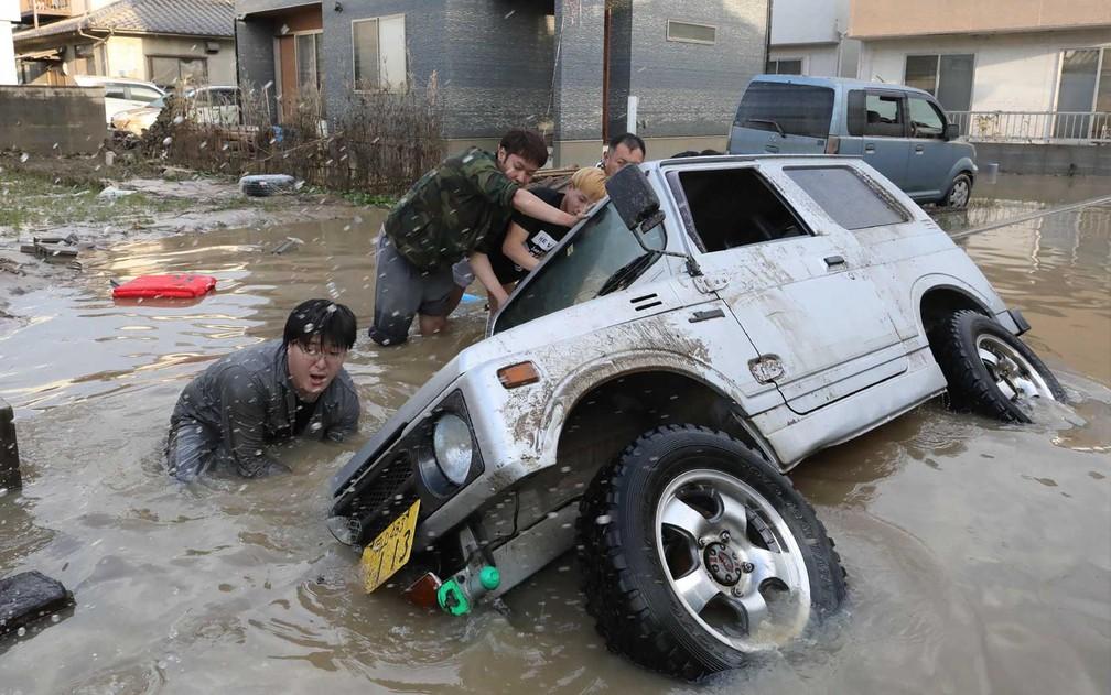 Moradores tentam erguer um veículo preso em uma área atingida pela enchente em Kurashiki, província de Okayama (Foto: Jiji Press / via AFP Photo)