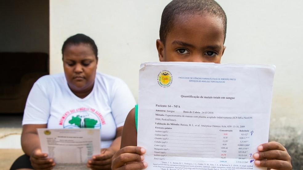 Apesar do diagnóstico, Andrea Domingos e o filho, Nicolas, não recebem contrapartida financeira da mineradora para arcar com o tratamento — Foto: Tainara Torres/BBC Brasil