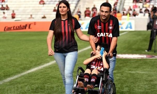 Rafael e seus pais no campo da Arena da Baixada