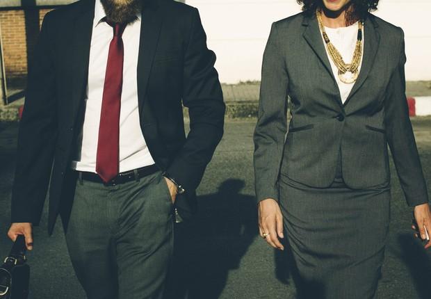Homem e mulher executivos andam lado a lado (Foto: Pexels)