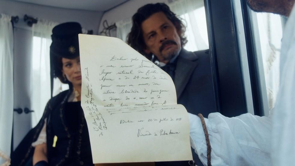 Luísa (Mariana Ximenes) mostra a Tonico (Alexandre Nero) a carta de alforria de Jorge/Samuel (Michel Gomes) em 'Nos Tempos do Imperador' — Foto: Globo