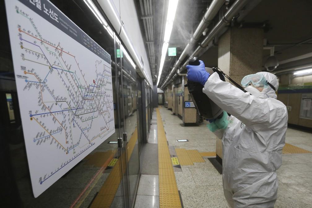 Agente usa desinfetante spray em estação de metrô em Seul, na Coreia do Sul, nesta sexta-feira (21), como tentativa de prevenir a disseminação do novo coronavírus. — Foto: Ahn Young-joon/AP