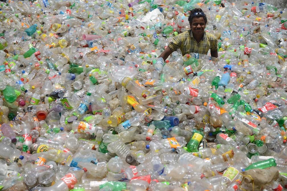 Homem trabalha separando garrafas de plástico num galpão em Jalandhar, na Índia (Foto: Shammi Mehra/AFP)