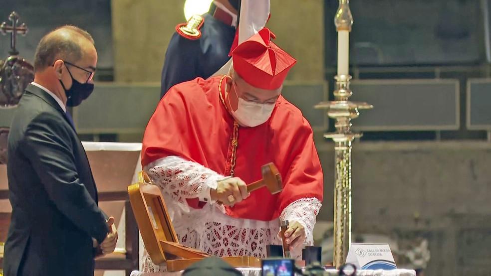 Cardeal-arcebispo do Rio, Dom Orani quebra um cunho da Medalha dos 90 anos do Cristo — Foto: Reprodução/TV Globo
