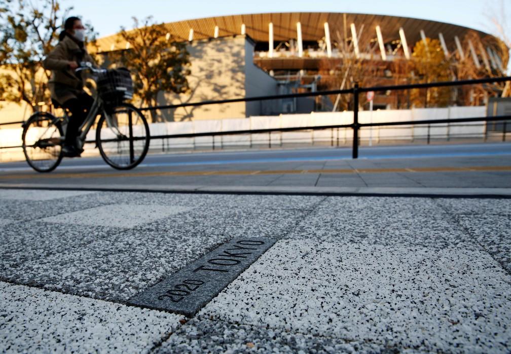 Ciclista passa em frente ao estádio de Tóquio onde devem acontecer as Olimpíadas — Foto: Kim Kyung-Hoon/Reuters