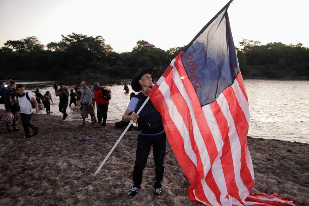 Migrante segura bandeira improvisada dos EUA logo após passar da Guatemala para o México nesta quinta-feira (23) — Foto: Andres Martinez Casares/Reuters