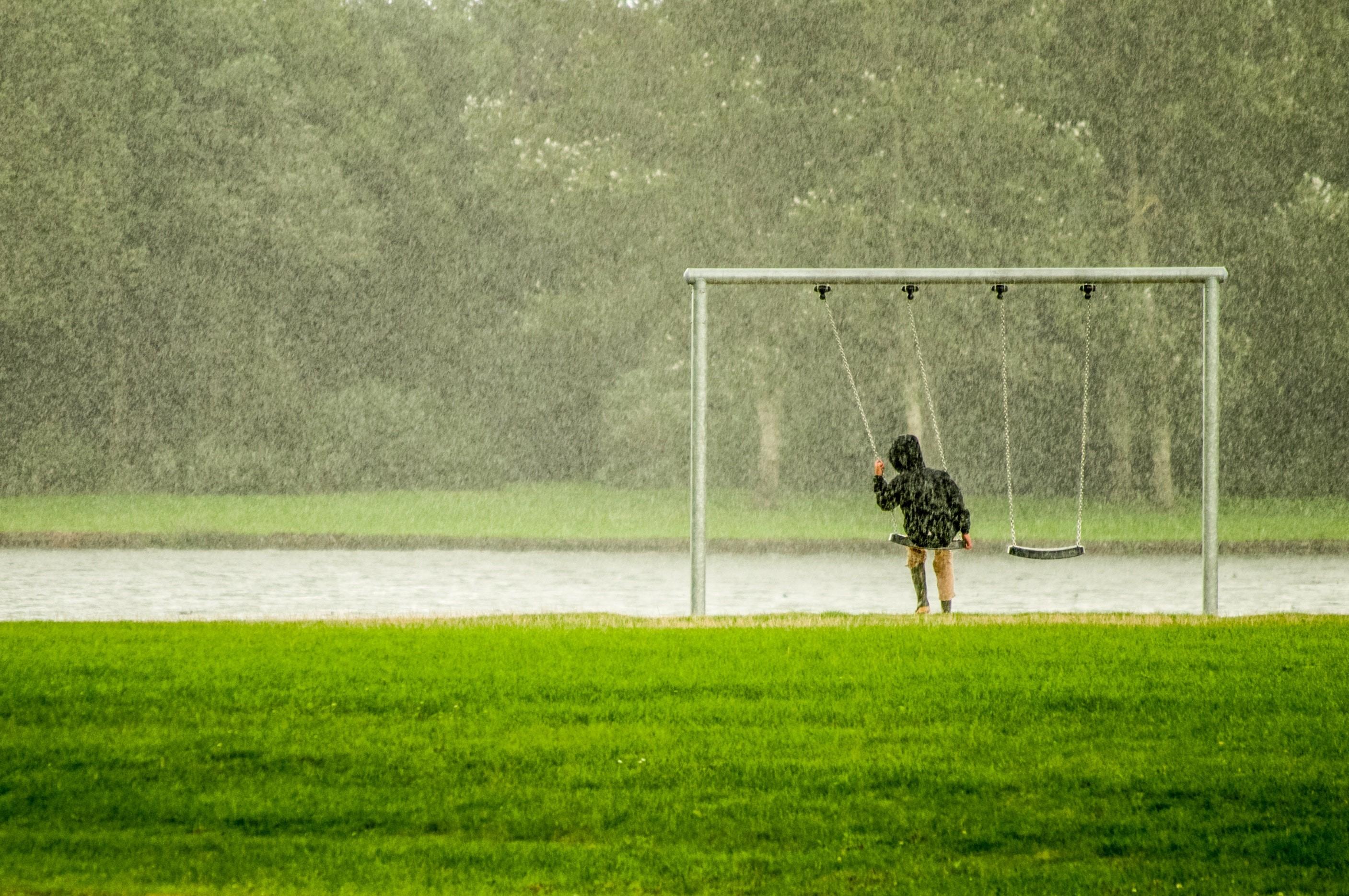 Criança toma chuva no parque enquanto brinca no balanço (Foto: Skitterphoto/Pexels)