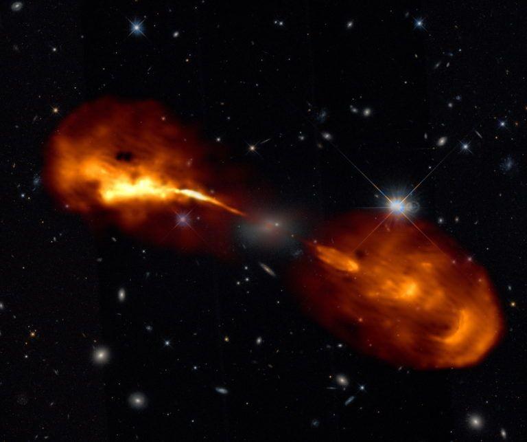 A galáxia Hércules A é alimentada por um buraco negro supermassivo localizado em seu centro, que se alimenta do gás circundante e canaliza parte desse gás em jatos extremamente rápidos. As novas observações de alta resolução feitas com o LOFAR revelaram que este jato fica mais forte e mais fraco a cada poucas centenas de milhares de anos. Essa variabilidade produz as belas estruturas vistas nos lobos gigantes, cada uma das quais é quase tão grande quanto a Via Láctea. (Foto: R. Timmerman; LOFAR & Hubble Space Telescope)