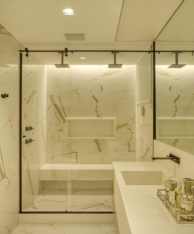 No banheiro da suíte, o Dekton aparece na bancada. Pisos e paredes foram cobertos com porcelanato idêntico ao mármore calacata, opção mais barata, resistente e fácil de manter (Foto: MCA Estúdio/Divulgação/Produção: Núria Uliana)