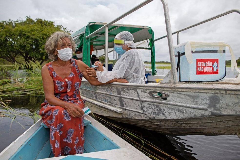 Olga D'arc Pimentel, de 72 anos, recebe dose da vacina de Oxford contra a Covid-19 em barco no Rio Negro em Nossa Senhora do Livramento, comunidade perto de Manaus, no dia 9 de fevereiro. — Foto: Michael Dantas/AFP