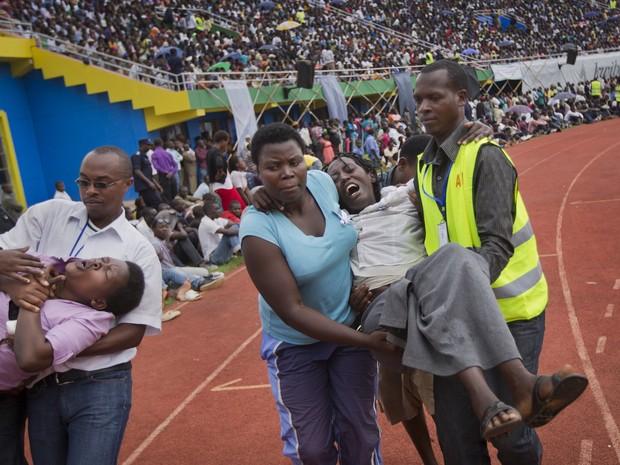 Mulheres passam mal durante uma cerimônia pública para marcar o 20 º aniversário do genocídio de Ruanda, no estádio Amahoro  (Foto: Ben Curtis/AP)