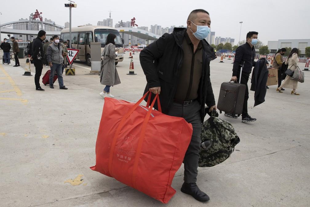2 de abril - Moradores carregam seus pertences enquanto passam por um pedágio para entrar na cidade de Wuhan, que ainda está trancada devido ao surto de coronavírus, mas começaram a permitir que alguns moradores retornem à província de Hubei, no centro da China — Foto: Ng Han Guan/AP