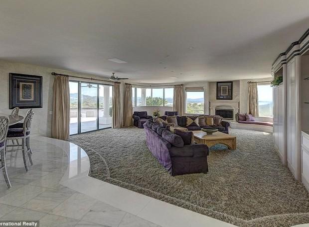 A cozinha fica ligada à uma sala que é iluminada por janelas grandes