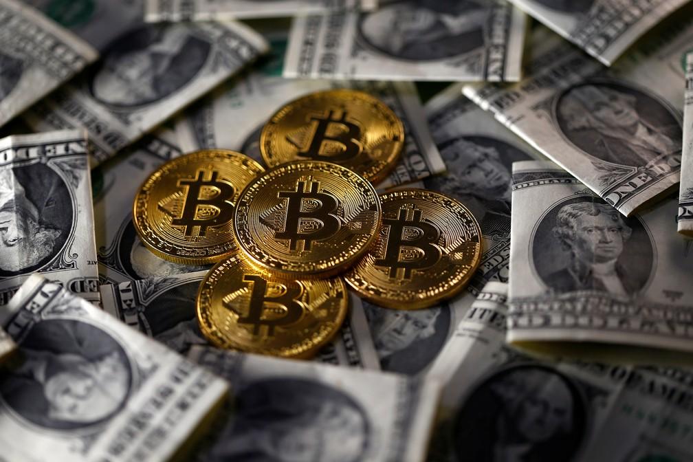 Moeda ilustrativa de bitcoin, em meio a notas de dólar. (Foto: Dado Ruvic/Reuters)