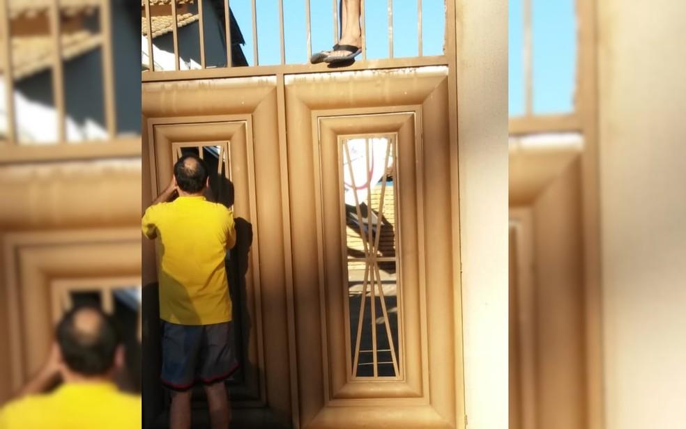 Foto mostra quando vizinha pula o portão para resgatar ocupantes de avião que caiu sobre casa em Goiânia, Goiás (Foto: Arquivo pessoal/ Geovanna Rocha)