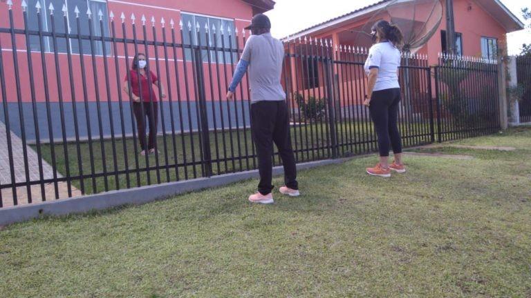 Separados pelo portão, idosos se exercitam com professores no quintal de casa, em Guarapuava