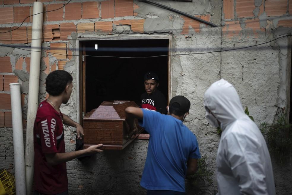 9 de maio de 2020 - Parentes ajudam trabalhador do serviço SOS Funeral a remover caixão com o corpo de Eldon Cascais durante a pandemia do novo coronavirus em Manaus, Brasil — Foto: Felipe Dana/AP