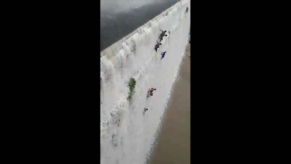 Homens tomam banho em paredão dee barragem, com 16 metros de altura, em Timbaúba, na Zona da Mata Norte de Pernambuco â?? Foto: João Marcolino/WhatsApp