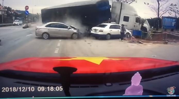 Esse frame do vídeo mostra a mãe (à direita) tirando o bebê do carro quando o caminhão (à esquerda) saiu do controle e bateu na barragem de segurança da rodovia (Foto: Reprodução Youtube)