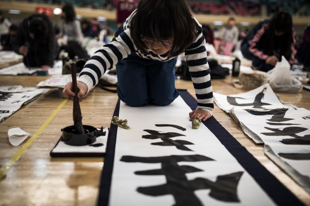 5 de janeiro - Participantes escrevem com caracteres japoneses durante um concurso anual de caligrafia em Tóquio (Foto: Behrouz Mehri/AFP)