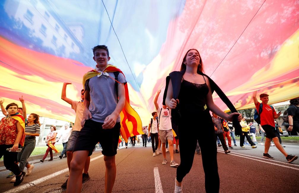 Manifestantes andam sob uma Estelada (bandeira separatista catalã) enquanto marcham na Avenida Diagonal durante greve geral da Catalunha em Barcelona, na Espanha, nesta sexta-feira (18)  — Foto: Albert Gea/ Reuters
