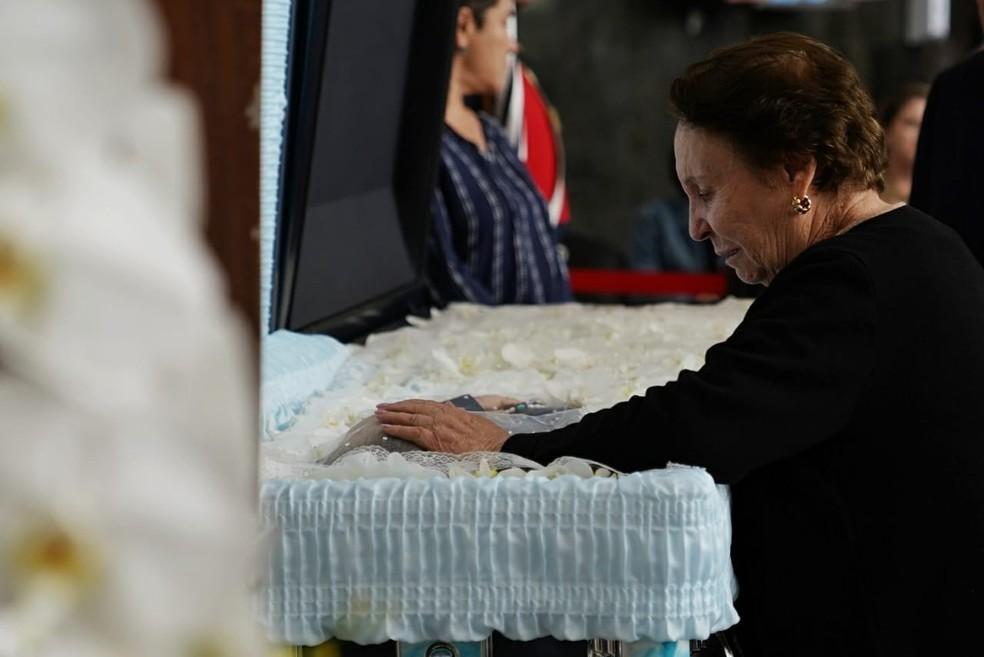 Mãe de Gugu, Maria do Céu, chora ao ver corpo do filho na Alesp. Ela chegou de cadeira de rodas no salão, mas foi caminhando com ajuda de uma bengala até o caixão — Foto: Marcelo Brandt/G1