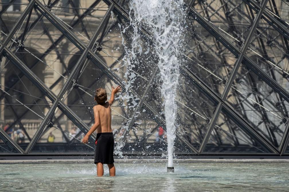 Criança brinca em fonte próxima à pirâmide do Museu do Louvre, em Paris. Cidade enfrenta onda de calor — Foto: Kenzo Tribouillard/AFP