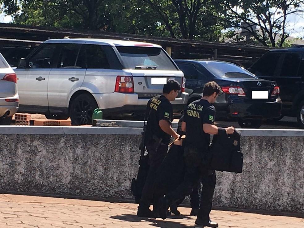 Policiais com malotes de apreensão. Ao fundo, três veículos apreendidos. Tudo na operação Ofir, em Campo Grande, MS (Foto: Alexandre Cabral/ TV Morena)