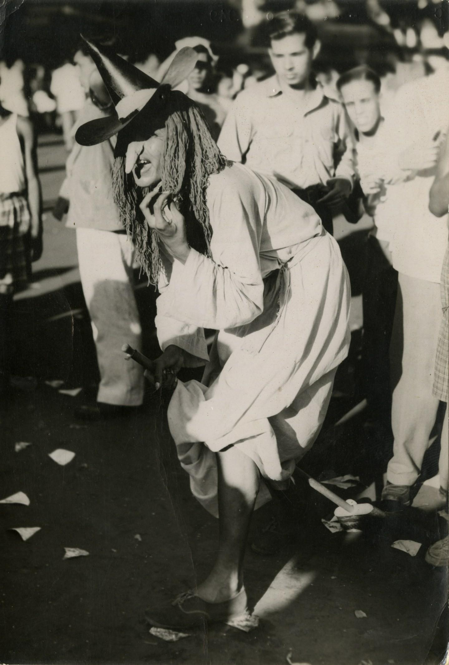 Folião se diverte vestido de bruxa durante o carnaval de 1949