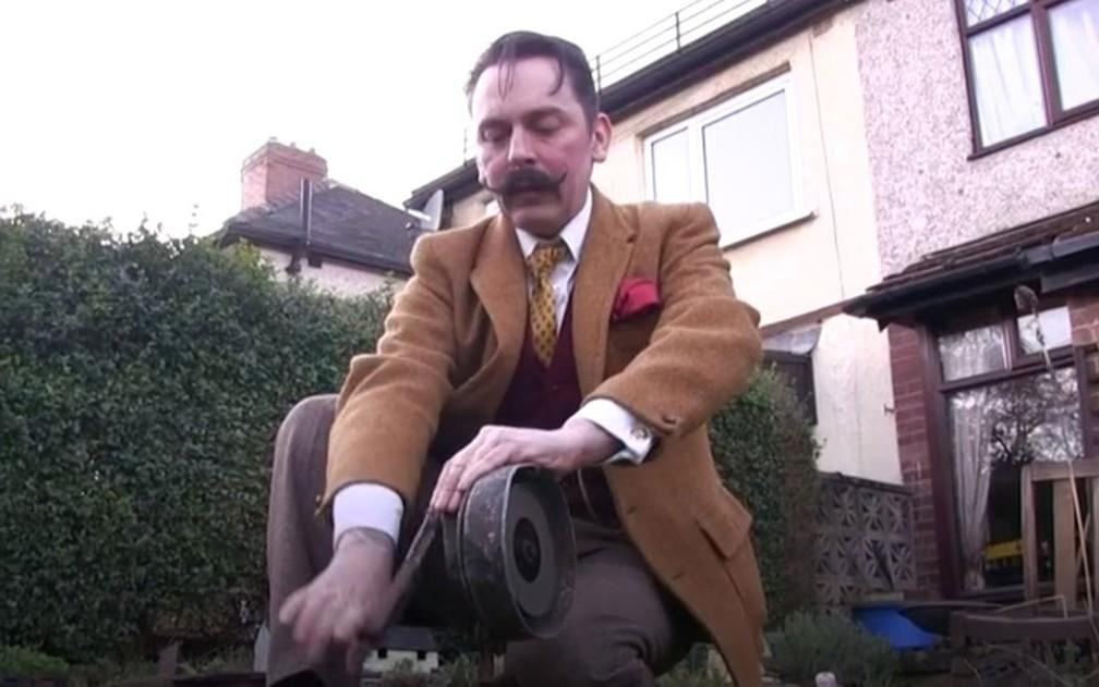"""Dean Turner em seu jardim """"retrô"""", ativando a sirene de ataques aéreos com uma manivela — Foto: BBC"""