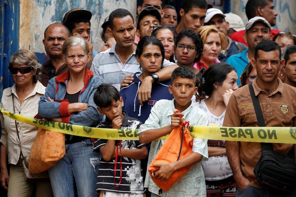 Moradores observam trabalho de investigadores em frente à padaria saqueada em Caracas (Foto: Reuters)