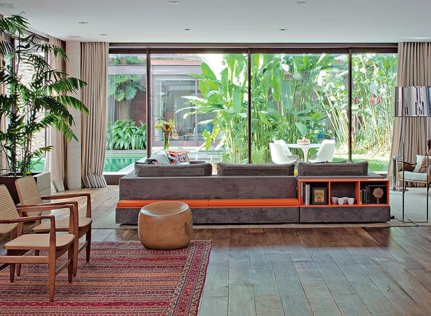 O sofá cinza tem um banco e módulos nas costas. Estes elementos dão um toque de cor vibrante, laranja, à decoração neutra. O modelo é uma boa opção para quem não vai encostar os assentos na parede. Projeto do Estúdio Cada Um (Foto: Luis Gomes/Casa e Jardim)