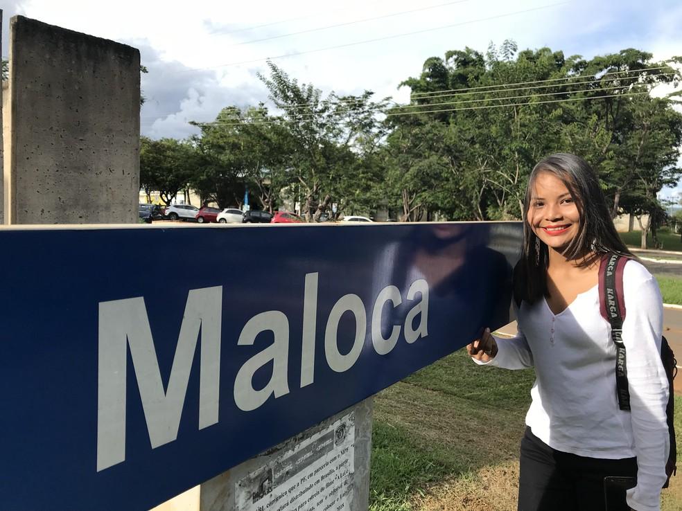 Indrig Rodrigues, 20, posa ao lado da placa do centro de convivência indígena da UnB (Foto: Marília Marques/G1)