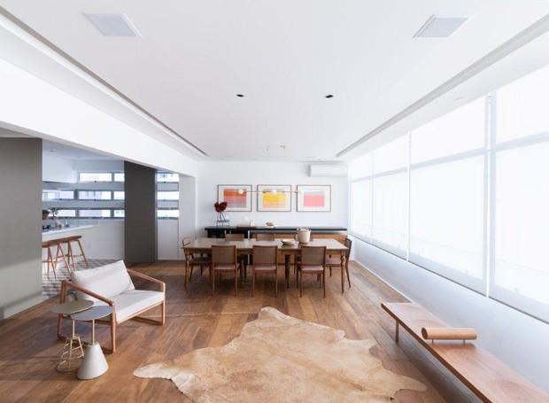 Rasgos no teto embutem as fontes de luz que se distribuem ao longo dos três ambientes da sala (Foto: Alexandre Disaro/Divulgação)