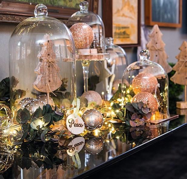 Festa no aparador: redomas maiores, árvores e enfeites de madeira deixam a decoração sofisticada
