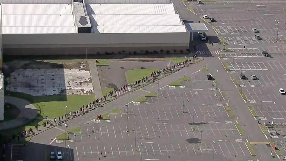 Longa fila se formou no estacionamento de shiopping para entrada na Caixa Econômica, neste sábado (22), para pagamento do auxílio pandemia e FGTS, em Paulista, no Grande Recife — Foto: Reprodução/TV Globo