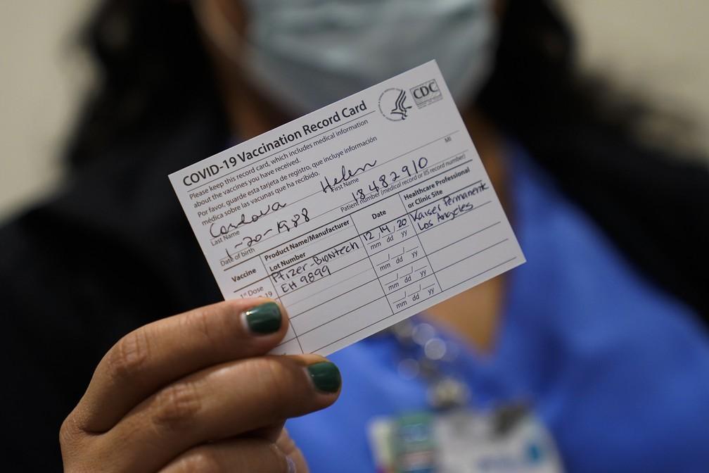 A enfermeira Helen Cordova mostra seu cartão de vacinação após receber a vacina da Pfizer no Kaiser Permanente Los Angeles Medical Center, em Los Angeles, nesta segunda-feira (14) — Foto: Jae C. Hong/AP