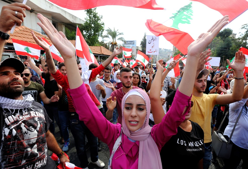 """Manifestantes agitam bandeiras libanesas e gritam """"o povo quer derrubar o regime"""" — Foto: Aziz Taher/Reuters"""