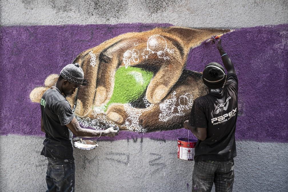 25 de março - Grafiteiros desenham mãos se lavando com sabão no muro de uma escola no bairro de Parcelles Assainies, em Dakar, no Senegal — Foto: Sylvain Cherkaoui/AP