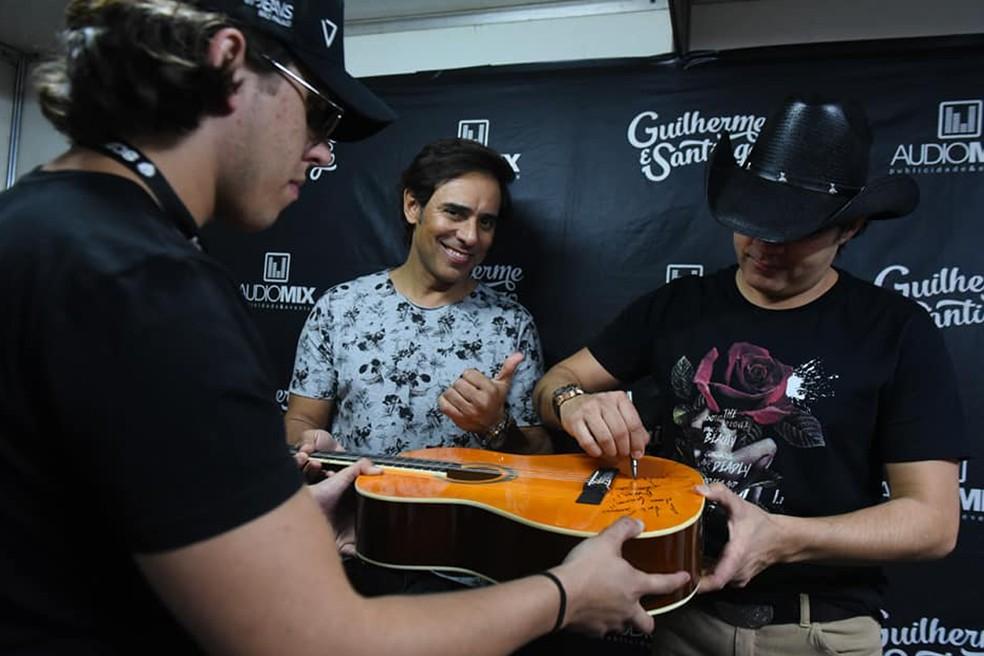 A dupla Guilherme & Santiago abriu o VillaMix Uberaba e autografou o violão, que será leiloado com renda revertida para o Hospital Hélio Angotti — Foto: ANDRÉ SANTOS