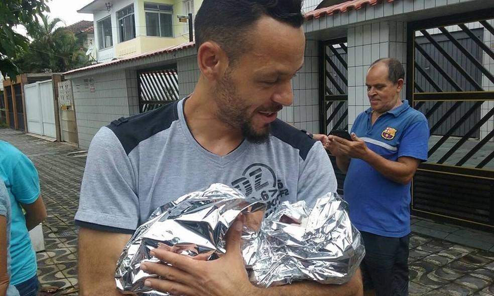 Xalaco com a pequena Mellany no colo, logo após o SAMU chegar no local (Foto: G1 Santos)