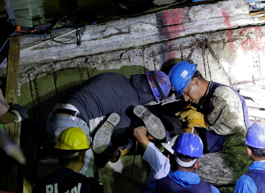 Socorrista entra sob escombros de escola Enrique Rebsamen, na Cidade do México, para procurar sobreviventes, nesta quinta-feira (21). Uma menina de 12 anos foi localizada com vida  (Foto: Daniel Becerril/ Reuters)